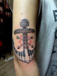 an anchor made of guitar and piano keys tattoo
