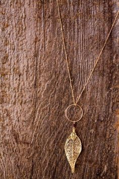 We adore how gold shimmers against rich wood.  https://www.etsy.com/listing/86318564/simple-leaf-necklace-gold-leaf-neclace