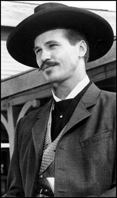 "Val Kilmer as Doc Holiday [Tombstone]  Billy: ""Why, it's the drunk piano player. You're so drunk, you can't hit nothin'. In fact, you're probably seeing double.""  Doc:  ""I have two guns.. one for each of ya."""