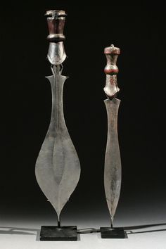 Africa | LEFT: Phoogo Ya Kusa Short Sword.  Wongo peoples, D.R. Congo | Forged iron, wood | Early 20th century.  And  RIGHT: A Foreign-Manufactured Blade Reforged into the Central African (Wongo) Style, Uganda | Forged iron, wood, nail, encrustation | Early 20th century