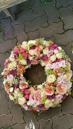 Een rouwkrans met een mix van verschillende rozen | Vind meer inspiratie over bloemen voor het afscheid en de uitvaart op http://www.rememberme.nl/rouwbloemen-rouwdecoratie/
