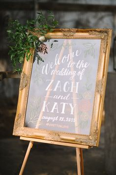 One of our most popular designs: gold framed glass/ acrylic insert wedding welcome sign. This sign is hand painted with calligraphy and hand lettering accented by custom flower drawings!