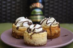 Creamy and boozy Mini Baileys Cheesecakes topped with drizzled chocolate and whipped cream.