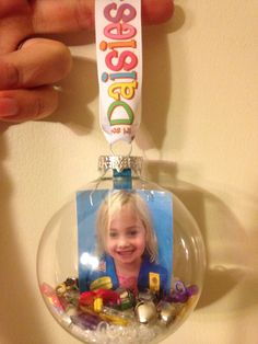 "Girl Scout Daisy ornament.  Glass ornament. Wallet sized photo (2 taped together so can see from both sides) with Popsicle stick that was cut - attached to photo so it stands up.  Filled with jingle bells, Daisy shaped buttons/beads and ""crystal snow"" (vase filler)."