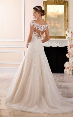 From Stella York, this off-the-shoulder lace wedding dress with sleeves is one-of-a-kind! Lace and tulle over Royal organza in a modern, modified A-line silhouette is a traditional take on a classic bridal look. The illusion lace back is complemented by illusion sleeves in an off-the-shoulder neckline, giving the front and back of the dress added drama. The lace motif continues onto the full tulle skirt creating a waterfall effect down through the train.