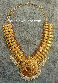 22 carat gold broad mango necklace from Mor Jewellers, featuring intricate design and studded with rubies. The necklace has pearl clusters hanging at its bottom. For inquiries contact: info Indian Jewellery Design, Latest Jewellery, Jewelry Design, Designer Jewelry, India Jewelry, Temple Jewellery, Antique Necklace, Antique Jewelry, Pendant Jewelry