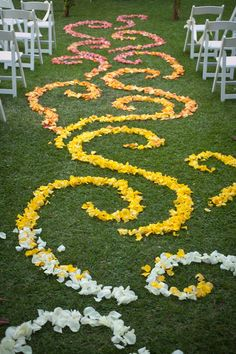 an intricate scroll pattern of flower petals is laid out on a green grass wedding aisle - thereddirtbride.com - see more of this wedding here