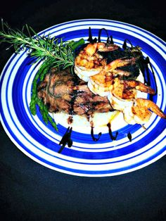 Hand-cut marinated ribeye served with skewered shrimp, asparagus, and garlic mashed potatoes at TC's Front Porch Navarre Florida, Navarre Beach, Lunches And Dinners, Meals, Shrimp Skewers, Garlic Mashed Potatoes, Outdoor Cafe, Front Porch, Asparagus