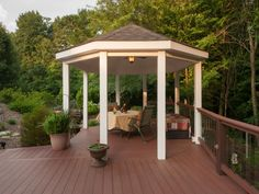 Kona and Redland Rose colors accent this design that uses Azek decking and custom railings with Decorator Frontier glass balusters to create the sense of an outdoor entertainment space nestled deep in the woods.