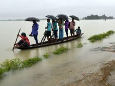 Indian villagers travel in a boat after their village was overtaken by floodwaters in Assam.  European Pressphoto Agency
