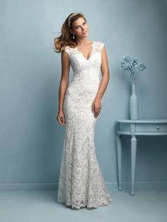 The Allure Bridals 9206 wedding dress is glamorous and alluring for the classic bride. The A-line satin gown has a floral lace overlay. The bodice features a plunging V-neck with sophisticated cap sleeves and a sheer lace back. The eyelash lace trim adds a touch of elegance. The gown has tiny buttons down the back and the lace flows into a soft chapel train. The gown is available in Cafe/Ivory, Ivory, and White.