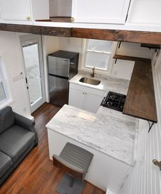 The kitchen has white and gray Quartz countertops, upper shelving, propane stove, two lazy Susans, refrigerator/freezer, and sink with antique bronze faucet.