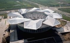 """Quizhong Tennis Center The magnolia-inspired roof of the Qizhong Tennis Center in Shanghai features dynamic roof """"petals"""" that can open and close depending on the weather."""