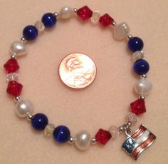 Stretch bracelet with red crackle glass beads, freshwater pearls, blue cats eye, clear AB beads, silver spacer beads, and American flag charm $25