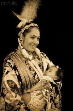 Mother Holds Baby in Arms. Native American mother dressed in traditional regalia holds her baby, (Shoshone-Bannock). Fort Hall, Idaho, USA. Marilyn Angel Wynn photography