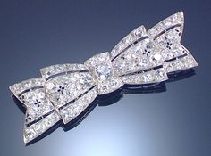 DIAMOND BROOCH ,1930S. Designed as a ribbon bow, the pierced geometric frame embellished with floral motifs and set with circular-cut and cushion-shaped diamonds.