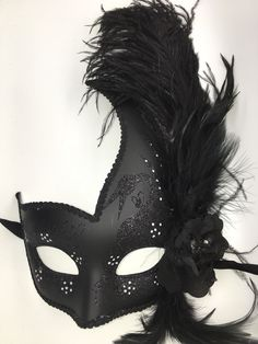 Black Venetian style Mardi Gras mask with feathers and ribbon ties.