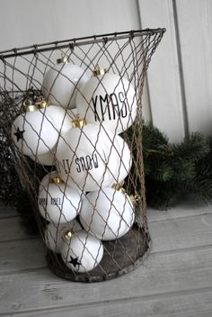 "Boules Collection ""White Christmas"" . Ornaments with simple black lettering, displayed in metal basket"
