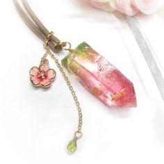 Theo(テオ)が見つけた、紅山桜のような色の水晶で作ったペンダントです。少し濃いめの桜ピンクと若葉の緑色が混ざったレジン鉱石をメインに、桜のチャームを合わせました。レジン鉱石には金箔入り。長めのワックスコードなのでニットなどの上からつけて、カジュアルにお使い頂けます。 「桜ハンドメイド2017」〈素材〉【紅山桜の水晶】樹脂 約40mm 金箔入り 【コード】ワックスコード 約70cm(5cmのアジャスター付)【ビーズ】チェコビーズ【チャーム】真鍮 ✳︎mimiriseのレジン鉱石は天然水晶から型取りして作成しているため、表面にクラック(亀裂や割れ目、節目)がありますが、天然鉱石の味としてそのまま使用しています。さらに作品によっては天然さざれ石を封入しており、さざれ石によっては、黒や茶の内包物が入っている場合があります。ご了承下さい。 ✳︎レジン作品は仕様上、気泡が含まれたり、サイズ・形などに多少のゆがみ、色味・表情の違いなどがあります。あらかじめご了承ください。作品の個性としてご理解頂けますと幸いです。…