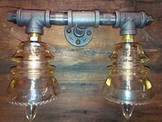 This unique and beautiful light has been fabricated using black steel pipe and connectors, two clear glass antique insulators, in mint