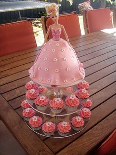 Gorgeous Barbie cake & cupcakes on a three tiered cupcake stand.  The cupcakes features a pretty pink frosting and flowers.  On the top of the stand sits a beautiful Barbie doll cake.