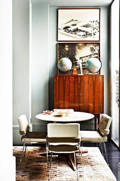 Hipster dining space with round table, Moroccan rug, Mid-century Modern cabinets, and framed art.