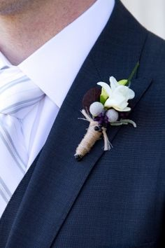 white freesia (perhaps to contrast with navy suit), silver brunia and purple berry accent?