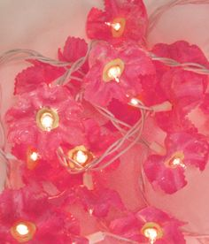 Flower bloom lights - made from the bottoms of soda bottles. I bet you could make them look like snowflakes, too. Very cool; I'd love to try these. I'm sure I have old Christmas lights in with my decorations in the attic!