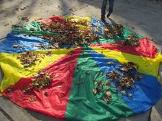 Outdoor fall parachute play in preschool. Collect leaves, sing a song... autumn leaves come falling down, red and yellow, golden and brown. Toss parachute.  (Hide under)