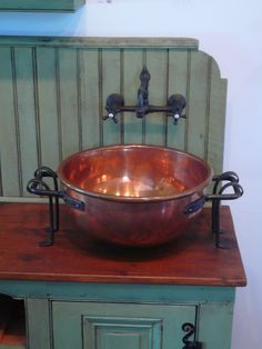 The sink is an antique copper candy kettle with wrought iron handles and supports and is ready for plumbing. The piece is made with antique lumber and old doors. A countertop made with reclaimed white pine boards is finished off with tung oil. This piece also sports two pairs of hand-wrought staghorn hinges. #Sink #Bathroom #Copper