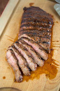 Juicy marinated flat iron steak just off the grill resting on cutting board | jessicagavin.com