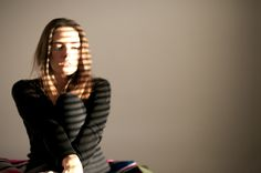 Light; In this image the warm light is being partially shaded by the blinds onto the womans face and arms. It also brightens the backround of the room.