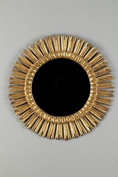 1970s circular mirror with gilded wood frame decorated with radiant motives.