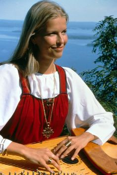 Finnish girl playing her kantele with a very Finnish background of lakes and forests