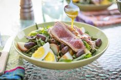This Ahi Nicoise Salad is served with boiled potatoes and seared tuna on top of a bed of spring greens, hardboiled eggs, and olives.
