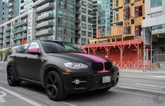 BMW X6 wrapped in Matte Black with Pink Stripes.
