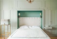 House tour: a 1930s Parisian-style apartment in Warsaw: In the master bedroom, white fabric on headboard by ROMO LINARA; Farrow & Ball paint in 'Light Blue' on built-in wardrobe; sconces found on eBay.