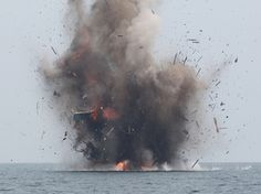 A foreign fishing boat that was caught in Indonesian territorial waters is blown up by Indonesian authorities in Kuala Langsa, Aceh Province on Tuesday. Indonesia sank more than 20 fishing boats Tuesday as part of a stepped up campaign against illegal fishing in its waters.