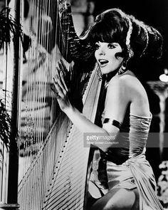 English actress Joan Collins playing a harp, as Lorelei Circe, aka Siren, in the…