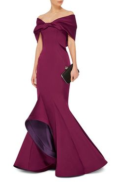 This **Zac Posen** gown is rendered in double face duchesse satin and features a mermaid silhouette with a wrap around off the shoulder neckline and a flounced asymmetrical hem.