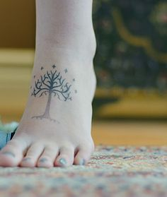 "I most definitely want a white tree of gondor tattoo, and the plan IS to get it on my foot. with ""not all those who wander are lost"" written next to it. i do LOVE how this one is done too. the fading and the color is perfect with this girl's skin color."