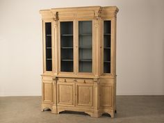 A handsome pale oak bibliothèque of breakfront form from France c. 1885 possessing the original antique glass doors and standing on bracket feet. Please notice the subtle manner employed by the designer of this bookcase to enhance its elegant tall appearance. The proportion of the cabinet doors on the top and bottom with their simple rectangular panels, are unbroken by any horizontal line. The pair of cabinet doors in the base each feature a raised panel with a moulded edge and are set…