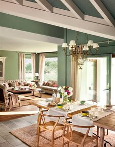 Salón comedor con paredes en verde y techo con vigas vistas