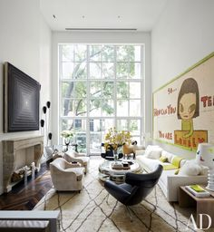 In the double-height family room of a New York townhouse, a 1965 Frank Stella canvas hangs over the mantel, while a painting by Yoshitomo Nara dominates the opposite wall. Living Room by Pamplemousse Design PHOTOGRAPHER: Björn Wallander and Oliver Cope Architect in New York, New York