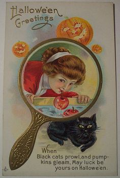 This card depicts the tradition of looking in a mirror, with a burning candle at midnight on Halloween, where the face of the one you will marry should appear. Some say to use the light of a jack-o-lantern with candle within.