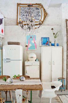 Cuisine avec réfrigérateur smeg, armoire ancienne en bois blanc, suspension en lustre, table en bois et siège type tolix, miroir avec dorure posé à l'horizontal