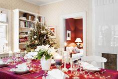 Jouluna Eeva kattaa pöydän kauniisti vanhoilla Arabian astioilla. Joululiina on Marimekon Mehiläispesä-kangasta. Eeva ja Aino ovat yhdessä koristelleet kuusen. Taustalla joulunpunainen olohuone.