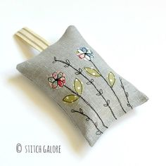Handmade grey linen lavender bag decorated with embroidered flowers and filled full of English lavender. www.stitchgalore.com