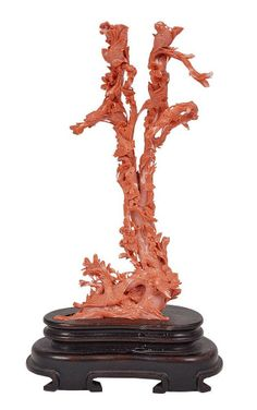 A CHINESE CORAL CARVING, EARLY 20TH CENTURY of flowering plum branches with birds both perched and flying about 25cm high excluding hardwood stand