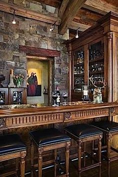 Straight home bar with four black leather seated stools built into a stone brick room with timber framing.